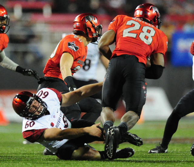 UNLV Rebels running back Keith Whitely (28) breaks the tackle of San Diego State Aztecs long snapper Jeff Overbaugh (60) while rushing in the second half of their NCAA Football game at Sam Boyd St ...