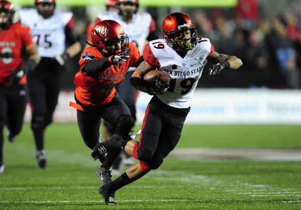 San Diego State Aztecs running back Donnel Pumphrey (12) breaks the tackle of UNLV Rebels defensive back Torry McTyer (4) in the first quarter of their NCAA Football game at Sam Boyd Stadium in He ...