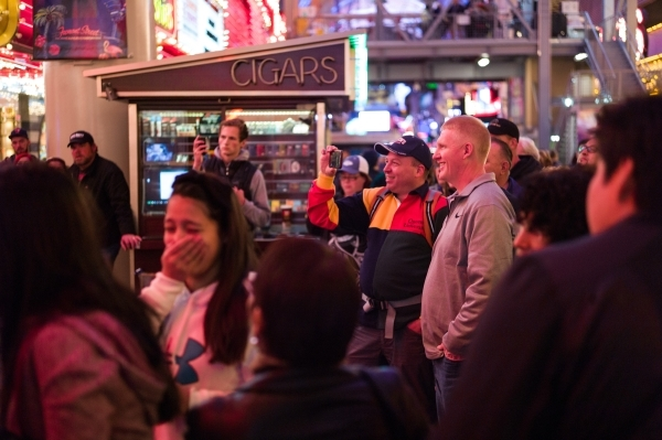 People watch magician Chris Randall perform on the Fremont Street Experience in downtown Las Vegas on Tuesday, Nov. 17, 2015. Tuesday was the first day of the city's new ordinance requiring  ...