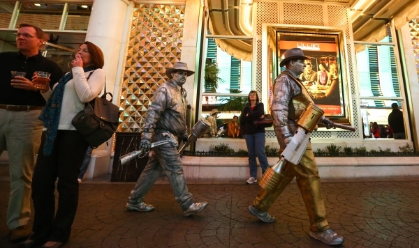 Street performers move to a new location zone on the Fremont Street Experience in downtown Las Vegas on Tuesday, Nov. 17, 2015. Tuesday was the first day of the city's new ordinance requirin ...