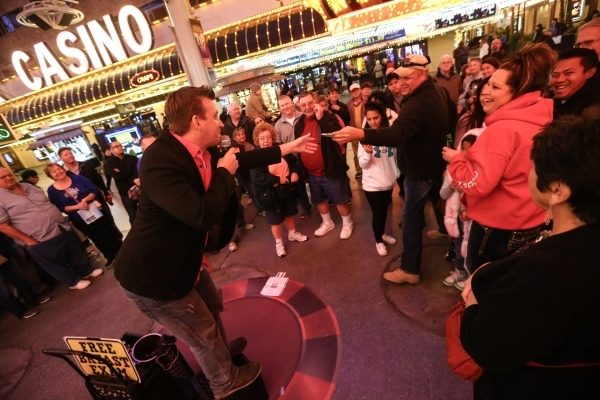Magician Chris Randall, left, takes a $100 bill from Shawn Ferrel of Missouri, at the Fremont Street Experience in downtown Las Vegas on Tuesday, Nov. 17, 2015. Tuesday was the first day of the ci ...