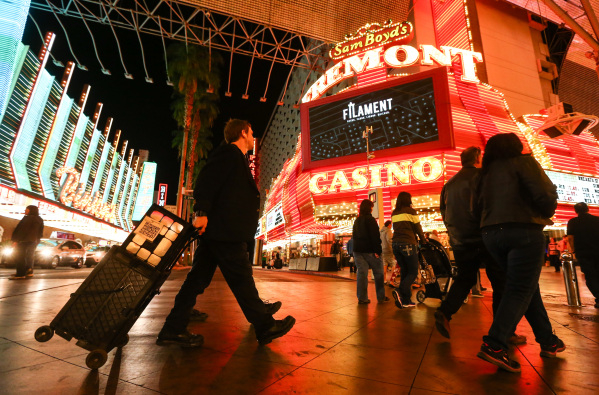 Magician Sean Scott, right, walks to a new location zone on the Fremont Street Experience in downtown Las Vegas on Tuesday, Nov. 17, 2015. Tuesday was the first day of the city's new ordinan ...