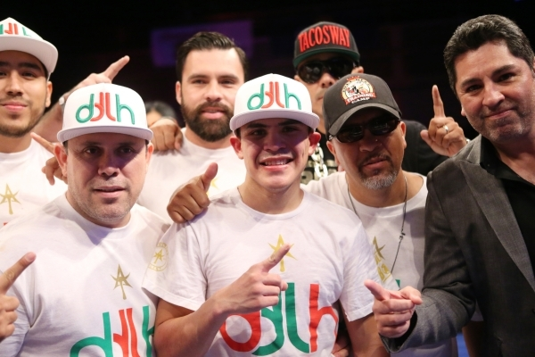 Diego De La Hoya, center, poses with his team after his unanimous win against Giovanni Delgado in their featherweight boxing bout at the Hard Rock casino-hotel in Las Vegas Friday, Nov. 20, 2015.