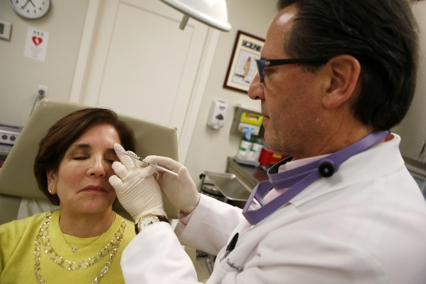 Howard Sobel, attending dermatologist and dermatologic surgeon at Lenox Hill Hospital in New York, demonstrates how botox or other anti-wrinkle medicines are applied via syringe to a patient at hi ...