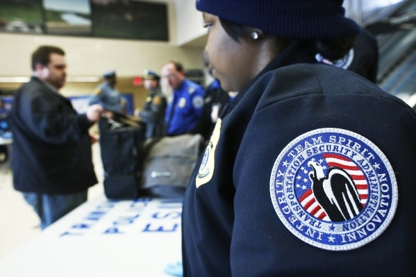Members of the Transportation Security Administration (TSA) check a passenger's bags with N.J. Transit Police to secure mass transit for the Super Bowl XLVIII, in Secaucus, New Jersey Januar ...