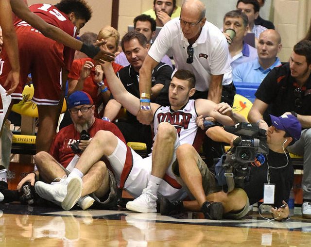 UNLV's Ben Carter is helped to his feet after tumbling into photographers and fans in the first half of Wednesday's game aganst Indiana at the Maui Jim Maui Invitational at the Lahaina Civic C ...
