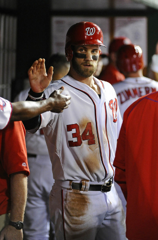Aug 26, 2015; Washington, DC, USA; Washington Nationals right fielder Bryce Harper (34) is congratulated by teammates after scoring a run against the San Diego Padres during the fourth inning at N ...