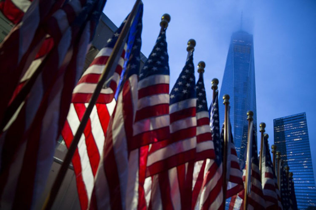 One World Trade Center is seen behind U.S flags on the morning of the 14th anniversary of the 9/11 attacks, in Lower Manhattan in New York September 11, 2015. . REUTERS/Andrew Kelly