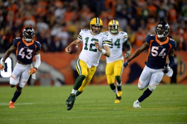 Nov 1, 2015; Denver, CO, USA; Green Bay Packers quarterback Aaron Rodgers (12) scrambles with the football in the third quarter against the Denver Broncos at Sports Authority Field at Mile High. T ...