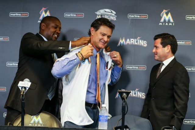 Nov 2, 2015; Miami, FL, USA; Miami Marlins president baseball operations Michael Hill (left) help smanager Don Mattingly (center) with his jersey as he is introduced as manager as Marlins presiden ...