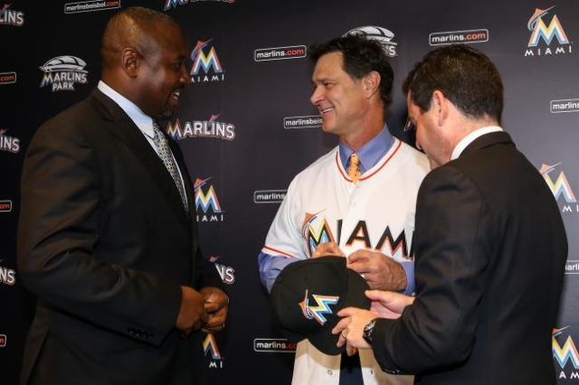 Nov 2, 2015; Miami, FL, USA; Miami Marlins manager Don Mattingly (center) talks with president baseball operations Michael Hill (left) and president David Samson (right) after a press conference a ...