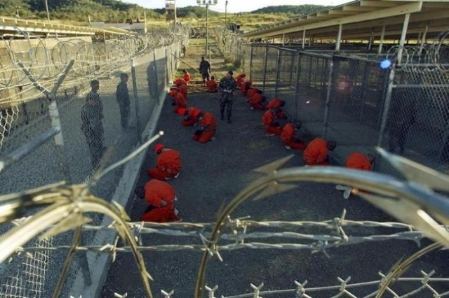Detainees in orange jumpsuits sit in a holding area under the watchful eyes of military police during in-processing to the temporary detention facility at Camp X-Ray of Naval Base Guantanamo Bay,  ...