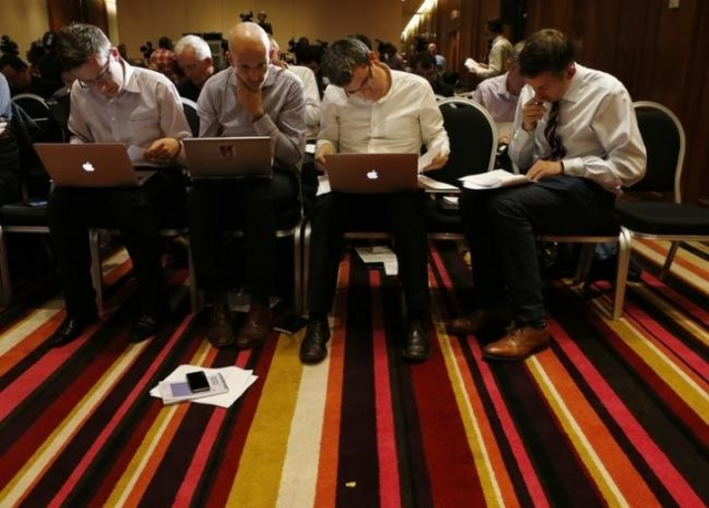 Journalists read the final report of World Anti-Doping Agency before a news conference on the WADA Independent Commission report on findings of investigation into allegations of widespread doping  ...