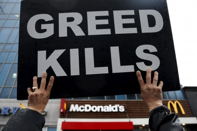 Fast-food workers and their supporters join a nationwide protest for higher wages and union rights outside McDonald's in the Harlem section of Manhattan in New York City, November 10, 2015.  ...