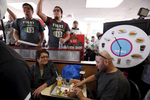 Vladimir Lopez, 40, (R) eats with his mother Ana Lopez, 62, inside a McDonald's restaurant as fast-food workers and their supporters protest for higher wages and union rights in Los Angeles, ...