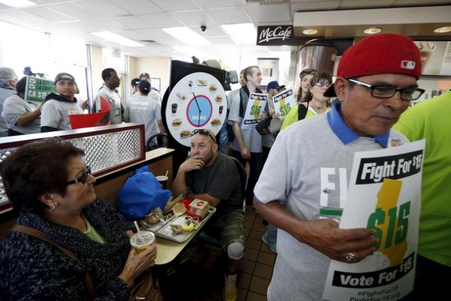 Vladimir Lopez, 40, (C) eats with his mother Ana Lopez, 62, (L) inside a McDonald's restaurant as fast-food workers and their supporters protest for higher wages and union rights in Los Ange ...