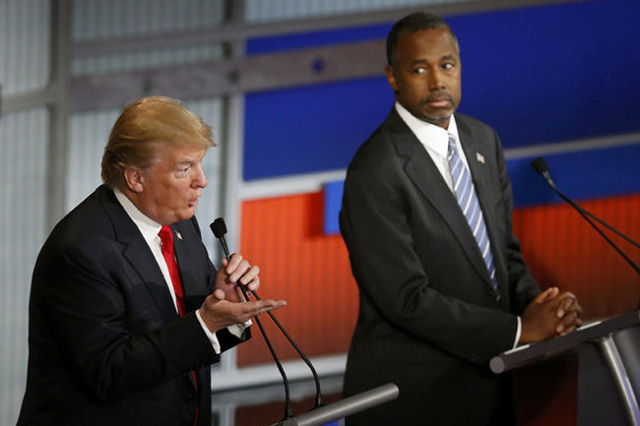 Republican U.S. presidential candidate and businessman Donald Trump speaks as rival candidate Dr. Ben Carson (R) looks on at the debate held by Fox Business Network for the top 2016 U.S. Republica ...