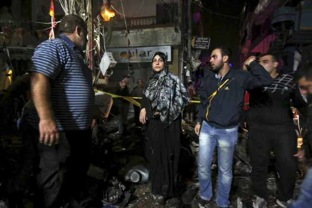 Residents inspect a damaged area caused by two explosions in Beirut's southern suburbs, Nov. 12, 2015. (Hasan Shaaban/Reuters)