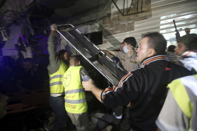 Civil Defense members carry a stretcher through a damaged area caused by two explosions in Beirut's southern suburbs, Nov. 12, 2015. (Hasan Shaaban/Reuters)