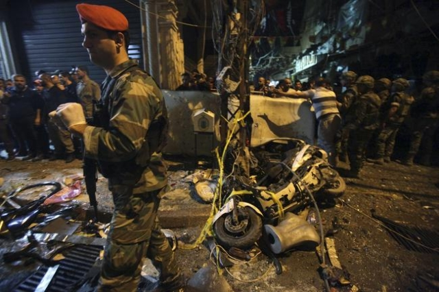 Residents and Lebanese army members inspect a damaged area caused by two explosions in Beirut's southern suburbs, Nov. 12, 2015. (Khalil Hassan/Reuters)