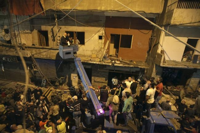Residents and Lebanese army members use a crane to inspect a damaged area caused by two explosions in Beirut's southern suburbs, Nov. 12, 2015. (Hasan Shaaban/Reuters)Nov. 12, 2015. (Khalil  ...