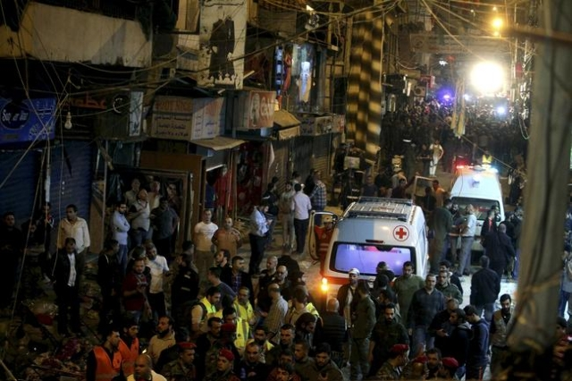 Red Cross vehicles drive by as residents and Lebanese army members inspect a damaged area caused by two explosions in Beirut's southern suburbs, Nov. 12, 2015. (Khalil Hassan/Reuters)
