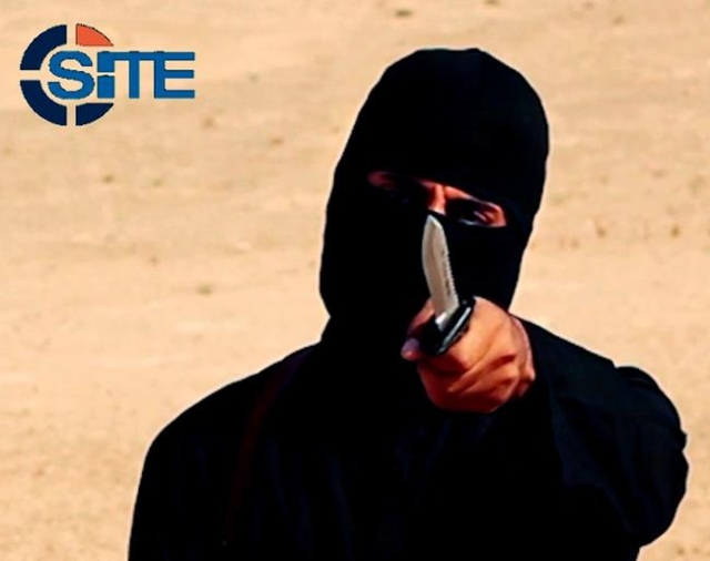 A masked, black-clad militant, who has been identified by the Washington Post newspaper as a Briton named Mohammed Emwazi, brandishes a knife in this still image from a 2014 video obtained from SI ...