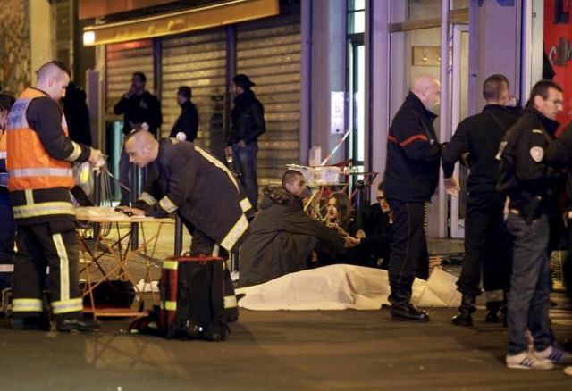 A general view of the scene that shows rescue services personnel working near the covered bodies outside a restaurant following a shooting incident in Paris, Nov. 13, 2015. (Philippe Wojazer/Reuters)