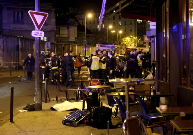 A general view of the scene that shows rescue services near the covered bodies outside a restaurant following a shooting incident in Paris, Nov. 13, 2015. (Philippe Wojazer/Reuters)
