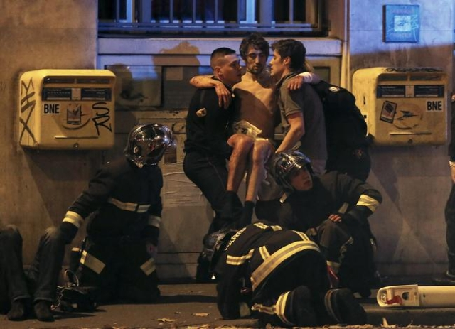 French fire brigade members aid an injured individual near the Bataclan concert hall following fatal shootings in Paris, Nov. 13, 2015. (Christian Hartmann/Reuters)