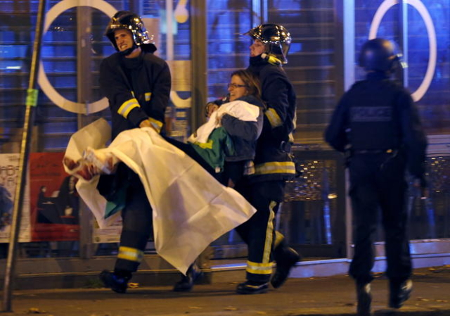 French fire brigade members aid an injured individual near the Bataclan concert hall following fatal shootings in Paris, France, November 13, 2015. (Christian Hartmann/Reuters)