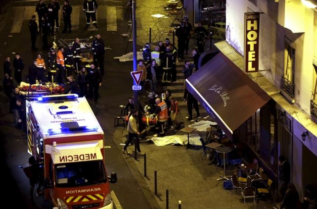 General view of the scene with rescue service personnel working near covered bodies outside a restaurant following shooting incidents in Paris, Nov.r 13, 2015.  (Philippe Wojazer/Reuters)