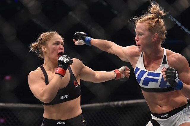 Nov 15, 2015; Melbourne, Australia; Ronda Rousey (red gloves) competes against Holly Holm (blue gloves) during UFC 193 at Etihad Stadium. (Reuters/Matt Roberts-USA TODAY Sports)
