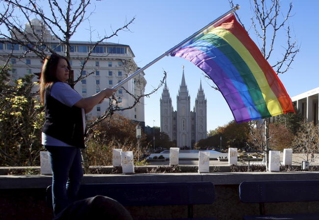 Sandy Newcomb stands with a flag near the Salt Lake Temple after members of The Church of Jesus Christ of Latter-day Saints mailed their membership resignation to the church in Salt Lake City, Uta ...