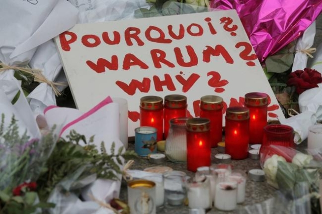 A sign asking why is seen amongst candles and flowers outside the Bataclan music hall following a series of shooting attacks on Friday in Paris, November 16, 2015. (Christian Hartmann/Reuters)
