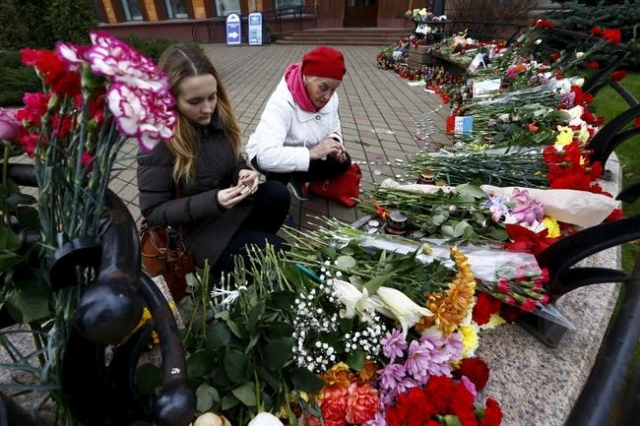 Women light candles to commemorate victims of the Paris attacks, in front of the French embassy in Minsk, Belarus November 16, 2015. (Reuters/Vasily Fedosenko)