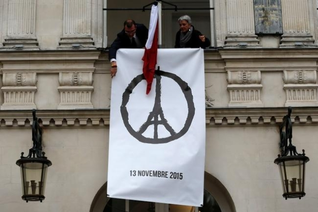 """Municipal employees deploy a banner with the drawing """"Peace for Paris"""" by French artist Jean Jullien as people observe a minute of silence at the city hall in Nantes, France, to pay trib ..."""