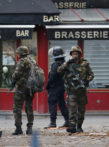 French soldiers and a special forces member secure the area as shots are exchanged in Saint-Denis, France, near Paris, November 18, 2015 during an operation to catch fugitives from Friday night&ls ...