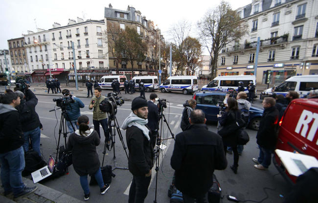 Journalists gather at the scene near police vans in Saint-Denis, France, near Paris, November 18, 2015 during an operation to catch fugitives from Friday night's deadly attacks in the French ...