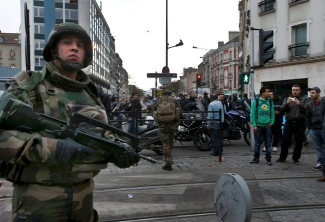 French soldiers secure the area as shots are exchanged in Saint-Denis, France, near Paris, November 18, 2015 during an operation to catch fugitives from Friday night's deadly attacks in the  ...