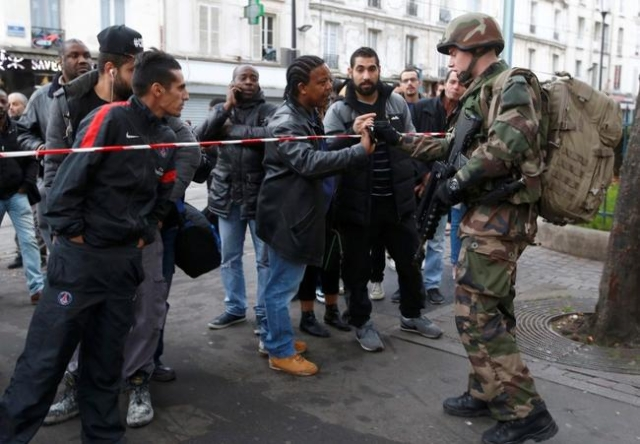 A French soldier checks the identity papers of a man in the area where shots were exchanged in Saint-Denis, France, near Paris, November 18, 2015 during an operation to catch fugitives from Friday ...