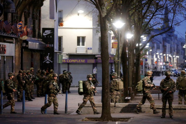 French soldiers secure the area after shots were exchanged in Saint-Denis, France, near Paris, November 18, 2015. (Reuters/Christian Hartmann)