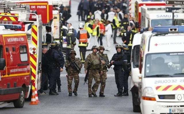French riot police (CRS), soldiers, firefighters, French red cross members and staff of the emergency medical services in France (SAMU) stand at the scene in Saint-Denis, France, near Paris, Novem ...
