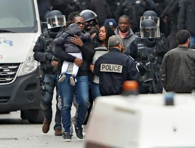 French special police forces evacuate family members from the building where police raided an apartment in Saint-Denis, near Paris, France, November 18, 2015 during an operation to catch fugitives ...