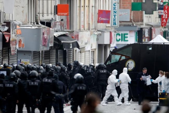 Members of French special police forces of the Research and Intervention Brigade (BRI) gather at the scene in Saint-Denis, near Paris, Nov. 18, 2015, during an operation to catch fugitives from Fr ...