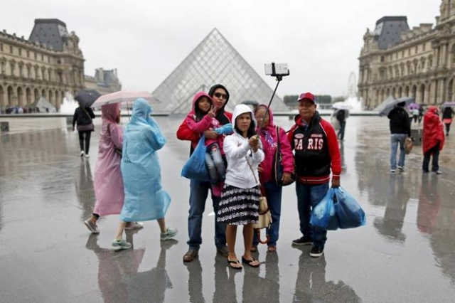 Tourists take a selfie near the Pyramid of the Louvre Museum on a rainy summer day in Paris, July 9, 2014. (Charles Platiau/Reuters/Files)