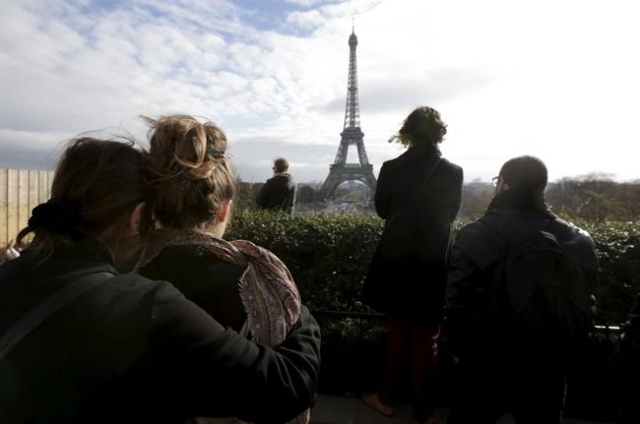 People observe a minute of silence at the Trocadero in front the Eiffel Tower to pay tribute to the victims of the series of deadly attacks on Friday in Paris, Nov. 16, 2015. (Philippe Wojazer/Reu ...