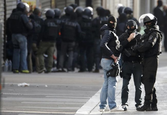 Members of French special police forces of the Research and Intervention Brigade (BRI) are seen near a raid zone in Saint-Denis, near Paris, Nov. 18, 2015, during an operation to catch fugitives f ...