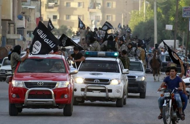 Militant Islamist fighters waving flags, travel in vehicles as they take part in a military parade along the streets of Syria's northern Raqqa province June 30, 2014. (Reuters)