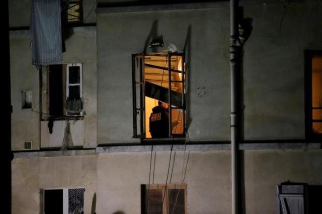 A member of French judicial police inspects the apartment raided by French Police special forces earlier in Saint-Denis, near Paris, Nov. 18, 2015, during an operation to catch fugitives from Frid ...